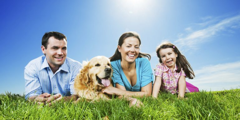 Happy family lying in the park with their dog.